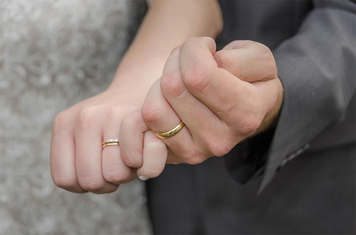 wedding rings and holding hands